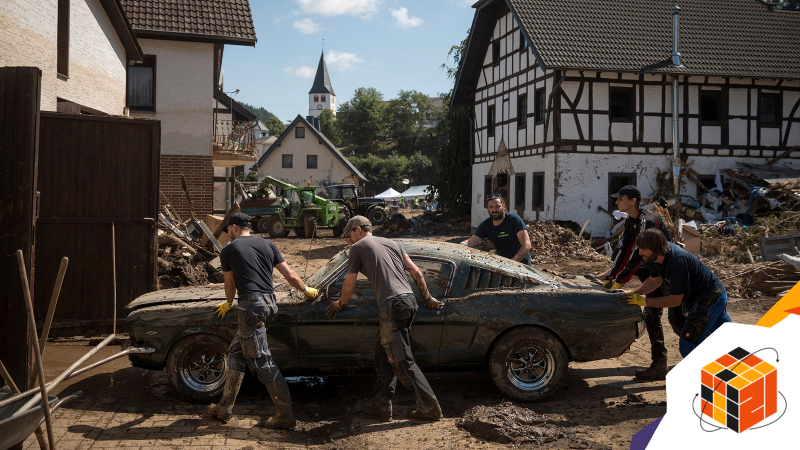 Men help move a car damaged by flooding in Schuld, Germany, July 18, 2021. (Gordon Welters/The New York Times)
