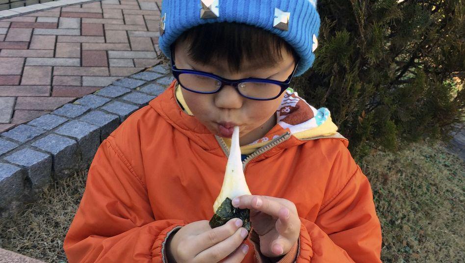 Potenziell lebensgefährlicher Neujahrs-Snack: japanisches Kind mit Mochi