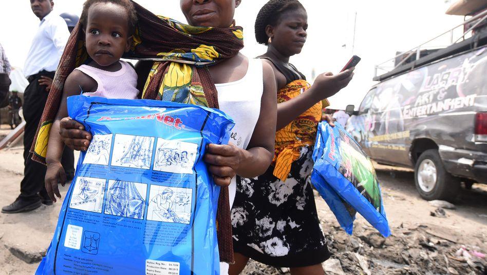 Frau trägt ein Kind und ein Moskitonetz