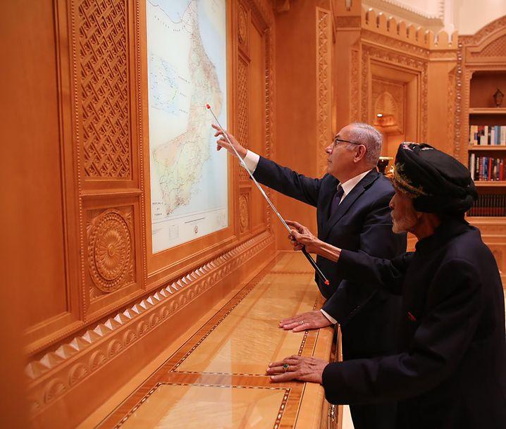 Benjamin Netanyahu und der Sultan von Oman betrachten eine Karte