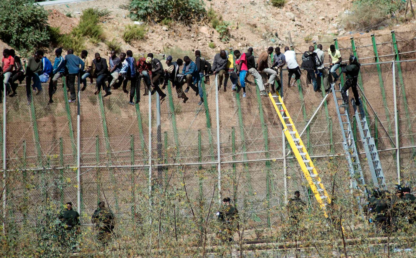 A Spanish Civil Guard officer helps an African immigrant to descend after he attempted to cross into Spanish territories
