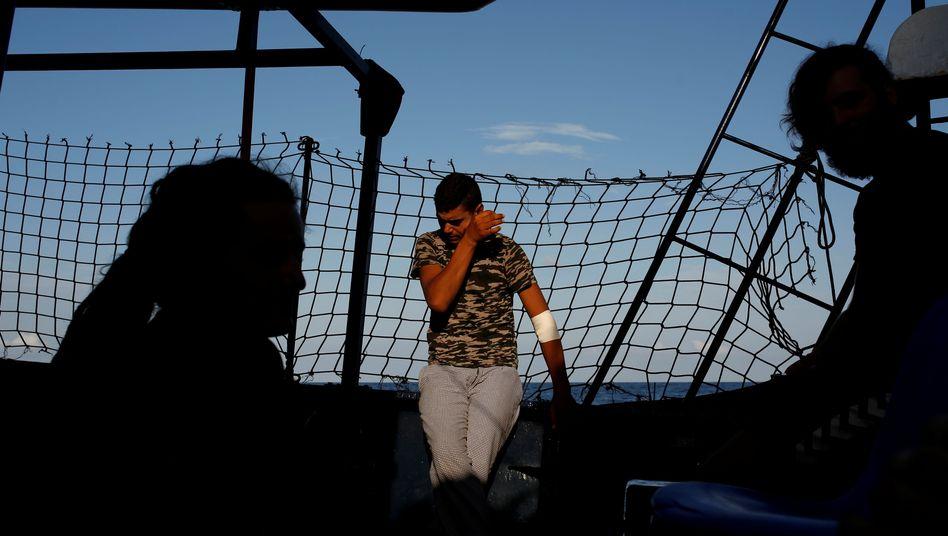 """Ein junger Migrant und zwei Crew-Mitglieder auf der """"Alan Kurdi"""""""