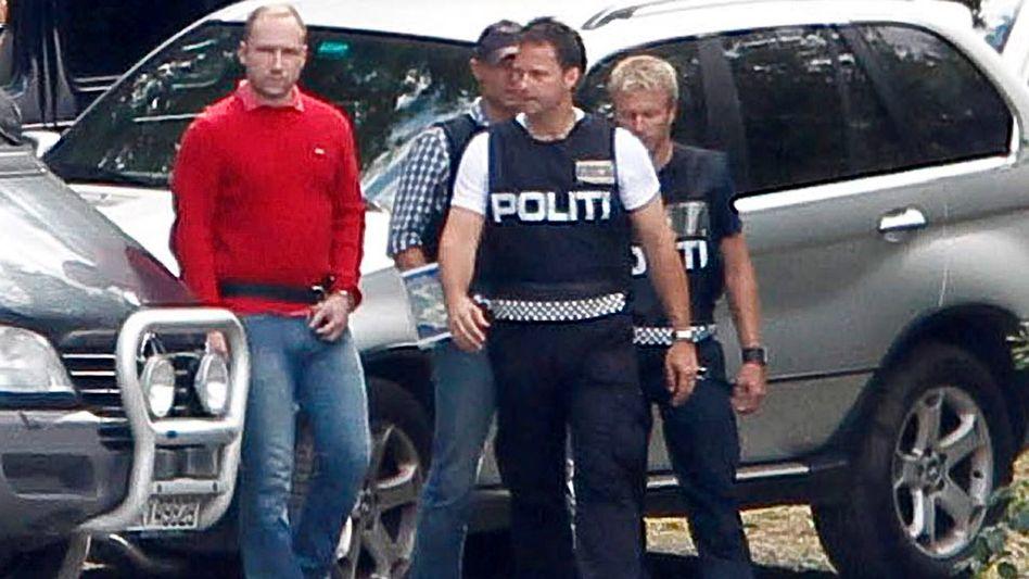 Polizisten bringen Breivik Mitte August nach Utøya, um den Tathergang zu rekonstruieren