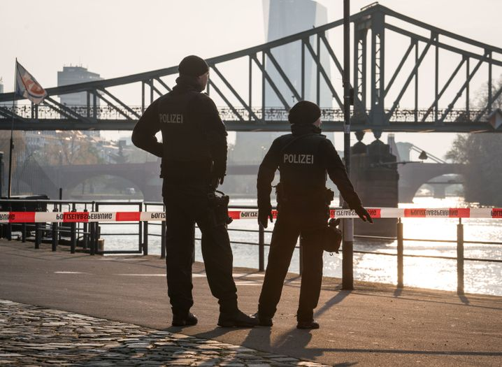Polizisten stehen morgens vor dem Eisernen Steg an einer Absperrung am Mainufer.