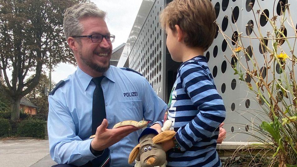 Polizist Patrick Schardt gibt die Schlange zurück – und einen Stoffhund dazu