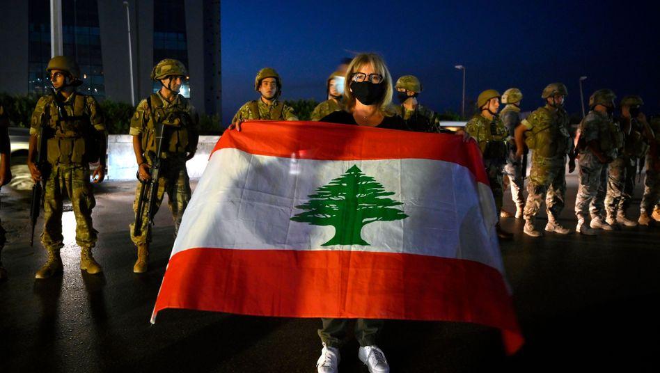 Protestlerin mit libanesischer Nationalflagge, Soldaten nördlich von Beirut (am 27. September): Die Stimmung ist niedergeschlagen
