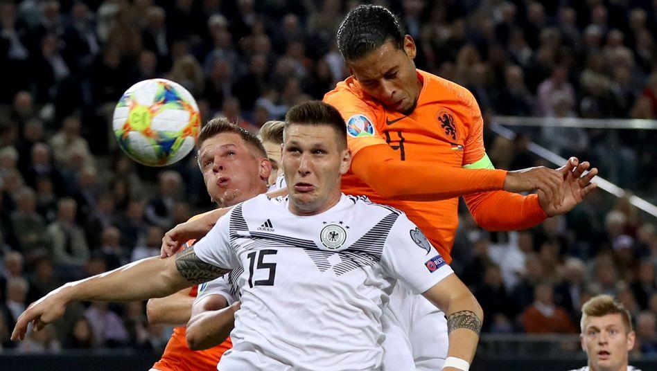 Niklas Süle (vorne) und Matthias Ginter verteidigen Virgil Van Dijk. Toni Kroos (r.)scheint Schlimmes zu ahnen