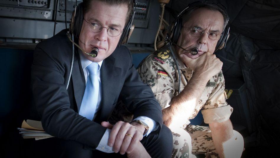 Defense Minister Karl-Theodor zu Guttenberg (left) and former Bundeswehr Inspector-General Wolfgang Schneiderhan (2.v.r.) during a flight to Kabul on Nov. 12, 2009.