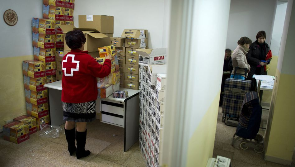 A Red Cross worker arranges boxes at a food distribution center in Villacanas, Spain.