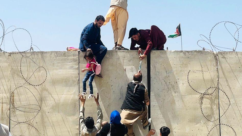 Afghanen versuchen, die Mauern am Kabuler Flughafen zu überwinden