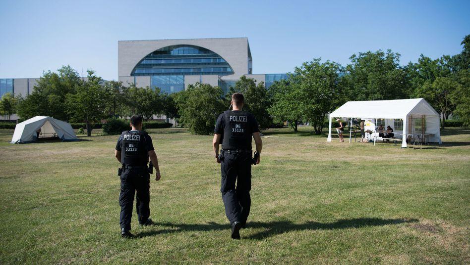 Polizisten gehen über das We4Future-Camp vor dem Bundeskanzleramt.