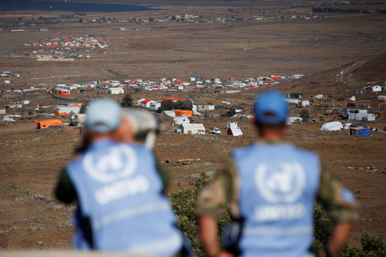 Peacekeeping troops from the unarmed United Nations Truce Supervision Organisation (UNTSO) look over the border line between Israel and Syria at a refugee tents erected at its Syrian side and seen from the Israeli-occupied Golan Heights