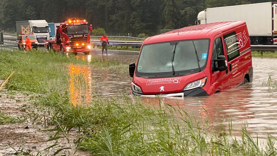 Ein Transporterfahrer hängt auf der A8 in Achenmühle mit seinem Fahrzeug im Hochwasser fest