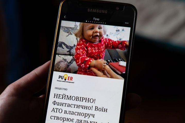 Serhij zeigt seine erste Puppe Weronika auf dem Smartphone
