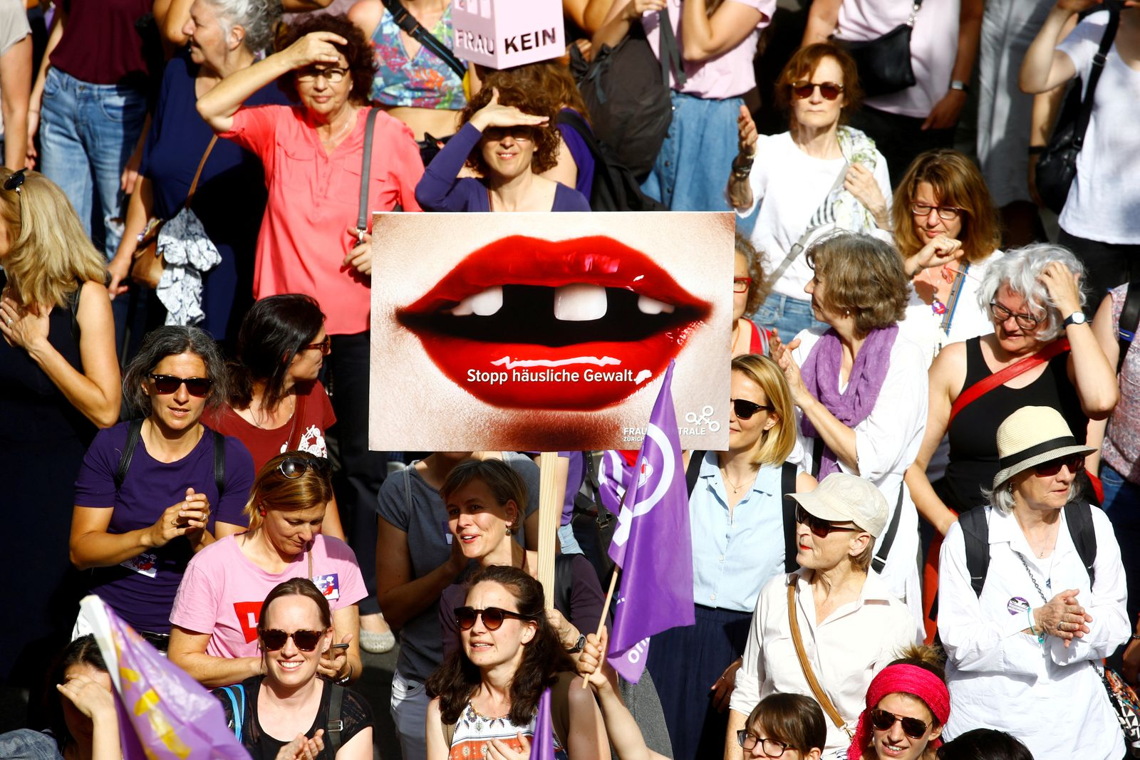 """FILE PHOTO: A protester carries a placard reading """"Stop domestic abuse"""" at a demonstration during a women's strike (Frauenstreik) in Zurich"""