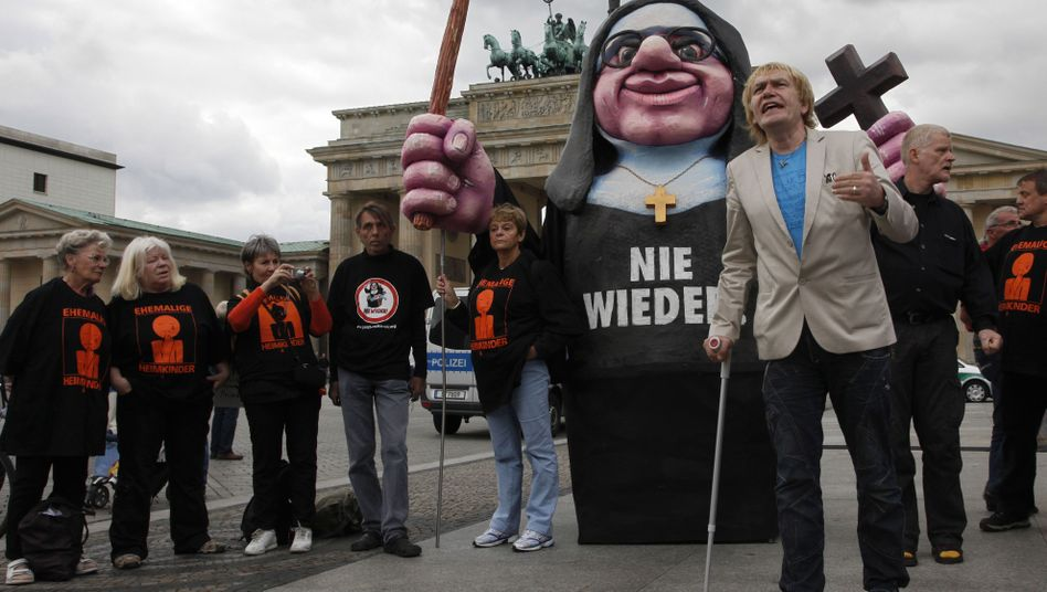 Anti-abuse activists protest in front of Berlin's Brandenburg Gate on Thursday.