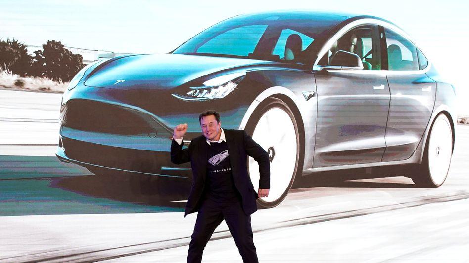 Große Bühne: Elon Musk vor einer Grafik des Tesla Model 3