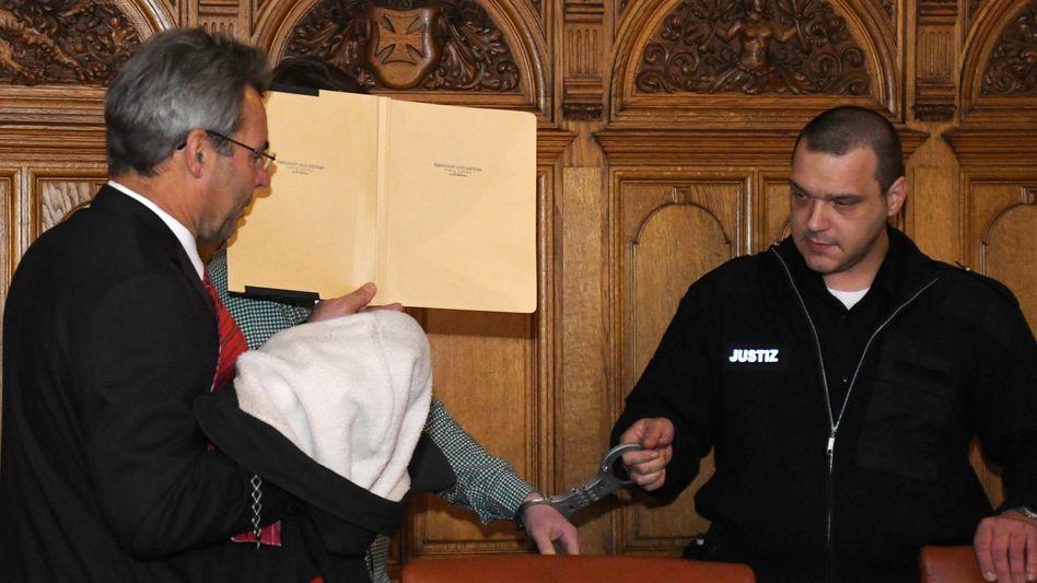 """Der Angeklagte """"Alpi"""" mit einem Verteidiger im Gerichtssaal"""