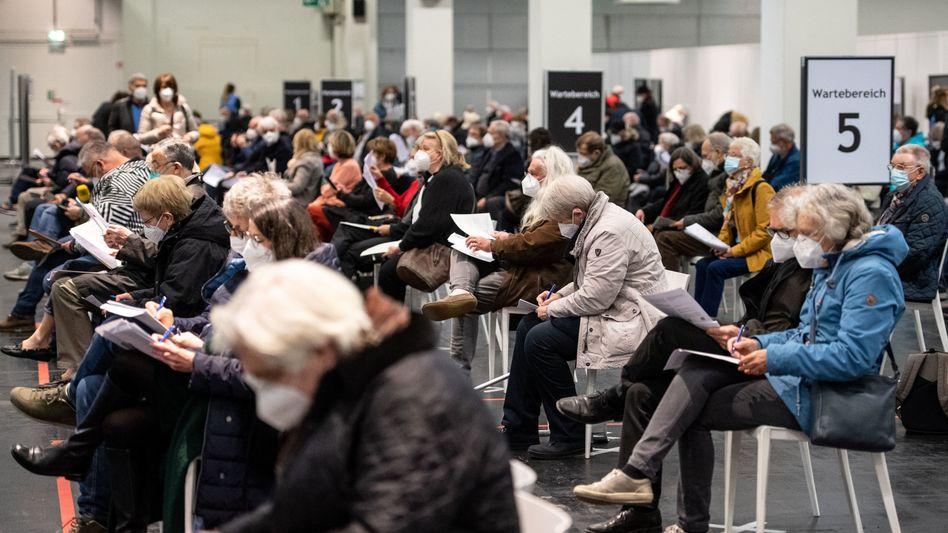 Menschen warten in einem Impfzentrum in Köln