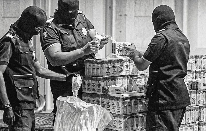 Investigators with confiscated drugs in Saudi Arabia