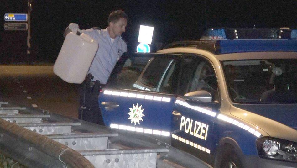 Erfolglose Jagd: Ein Polizist sichert einen Kanister, mit dem die Täter nachgetankt hatten