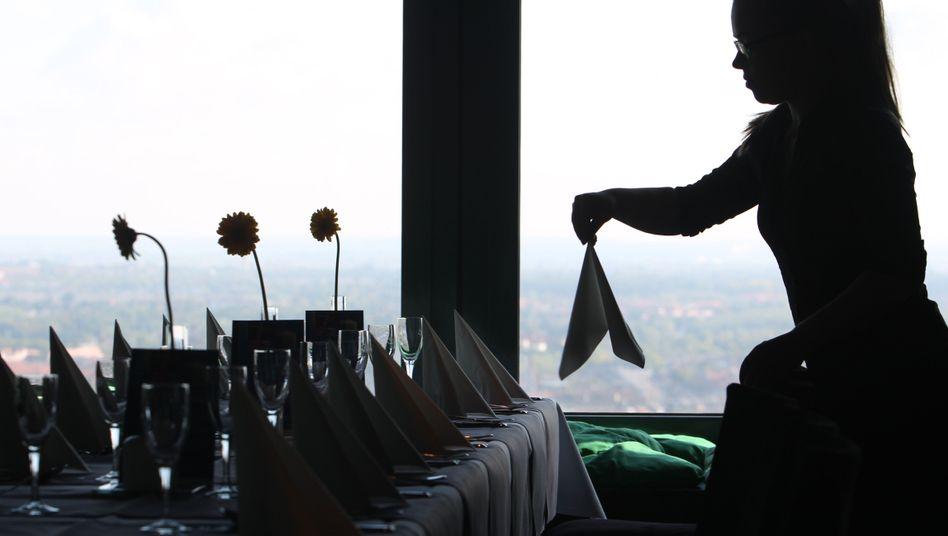 Eine Kellnerin deckt einen Tisch ein (Symbolbild)