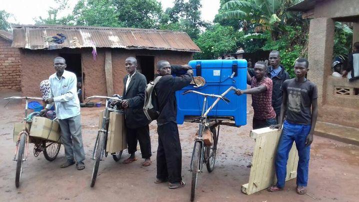 In einem Dorf in der Demokratischen Republik Kongo kommt eine Lieferung mit Impfstoff an – die medizinischen Thermoboxen werden auf Fahrrädern transportiert