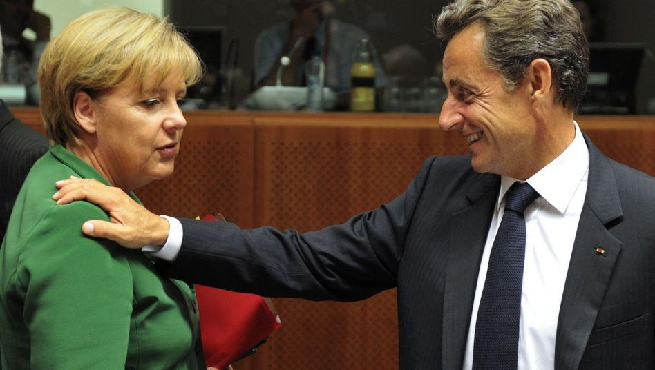 French President Nicolas Sarkozy speaks to German Chancellor Angela Merkel at the European Union summit in Brussels.