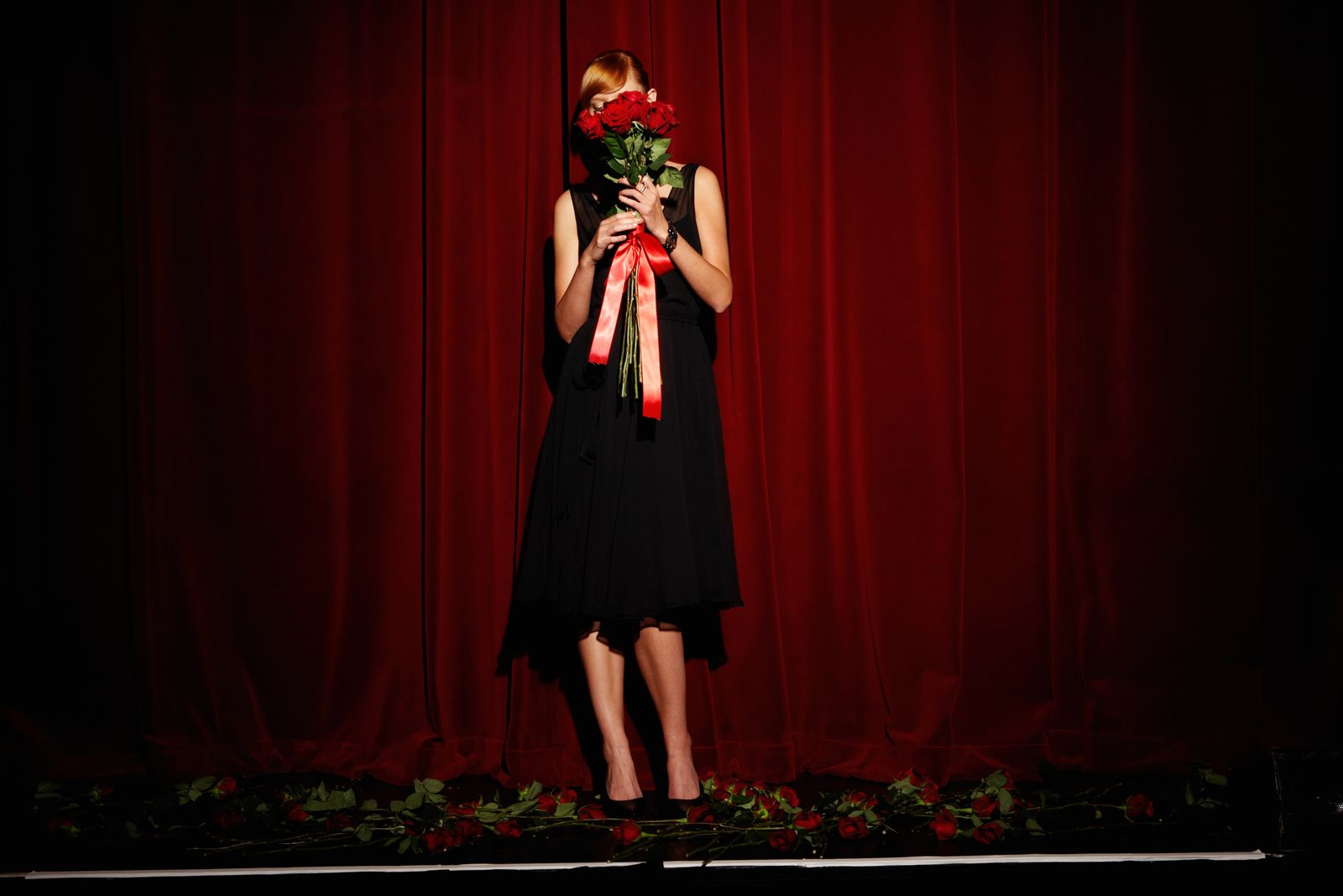 EINMALIGE VERWENDUNG Inrovertiert/ Arbeit - Young woman on stage holding red roses, low section