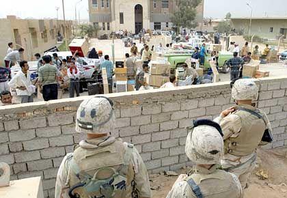 Das Volk nimmt, was des Volkes ist: US-Truppen sehen zu, wie Iraker ein Gebäude von Saddam Husseins Regierung plündern
