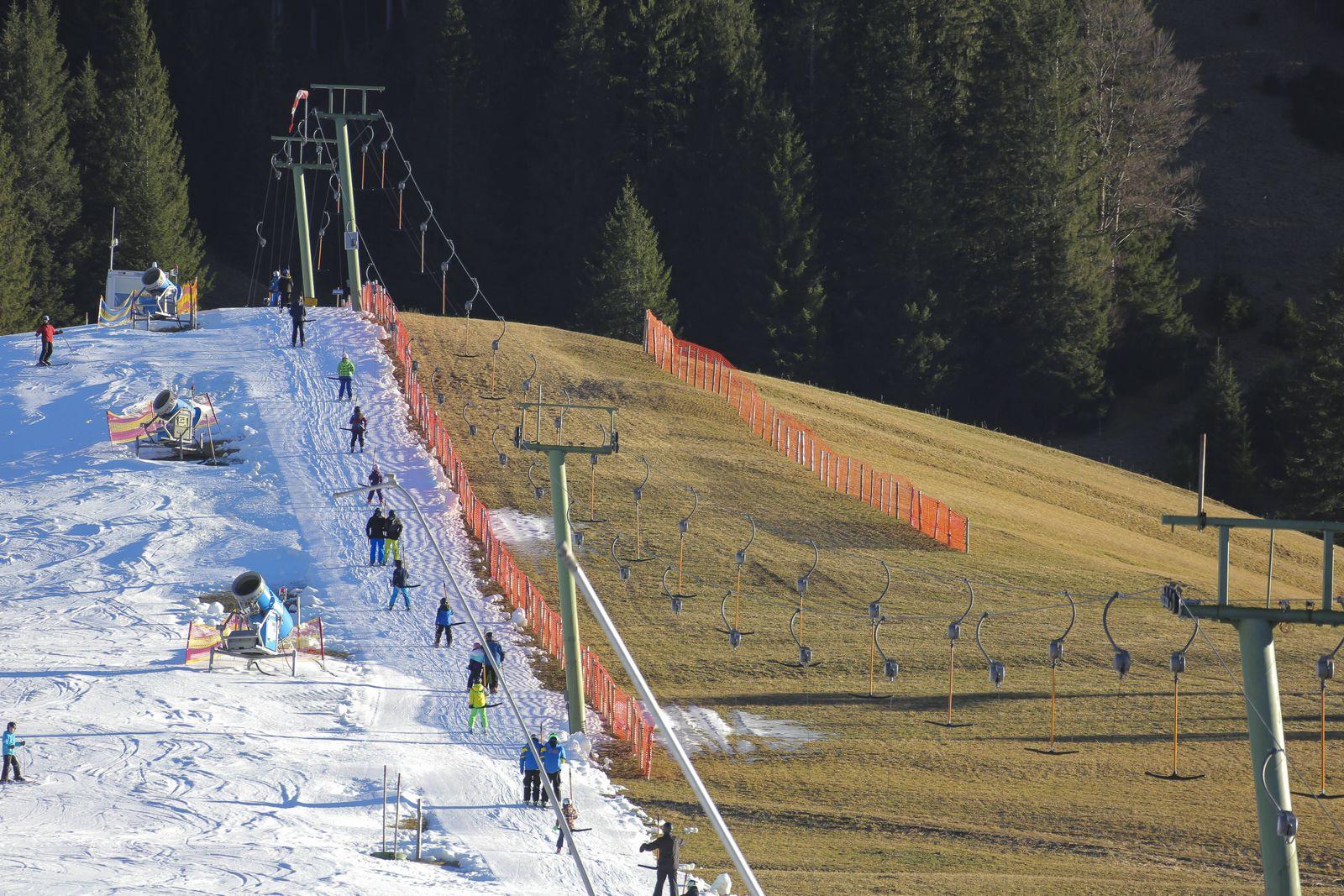 Wanderer Gleitschirmflieger und Skifahrer sind unterwegs bei warmen Temperaturen und Schneemangel t