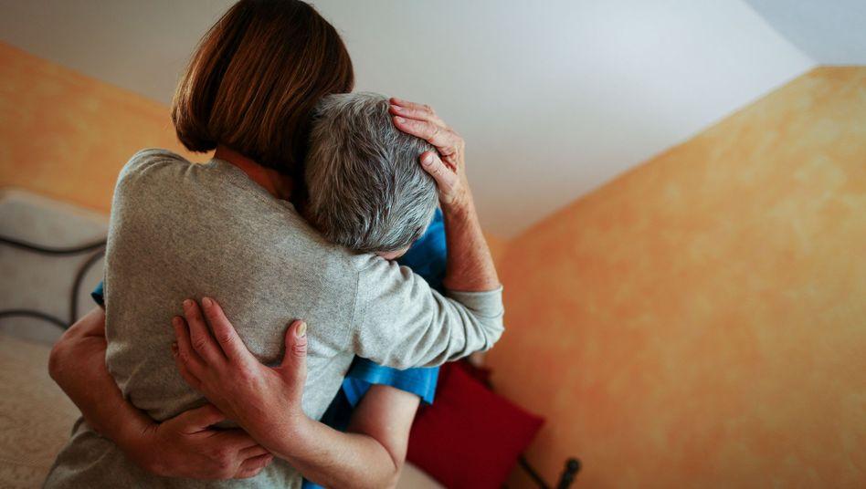 Eine Sexualbegleiterin umarmt und liebkost einen körperlich und geistig behinderten Kunden