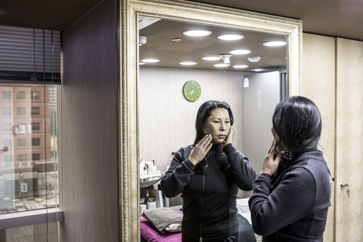 Kim Myeong Hye examines herself in the mirror after her treatment.