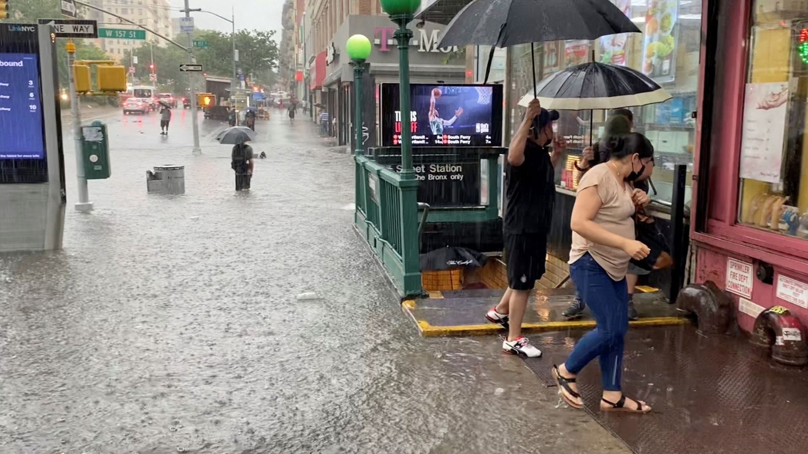 A person wades through the flood water near the 157th St. metro station in New York