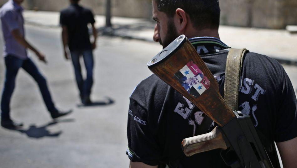Undurchsichtige Lage: Syrischer Armeesoldat mit Assad-Aufkleber an einem Checkpoint in Damaskus (Bild vom 21. August)