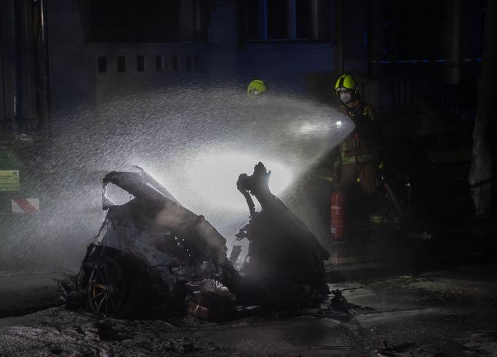 Einsatzkräfte der Feuerwehr löschen am Treptower Park in Berlin das Autowrack