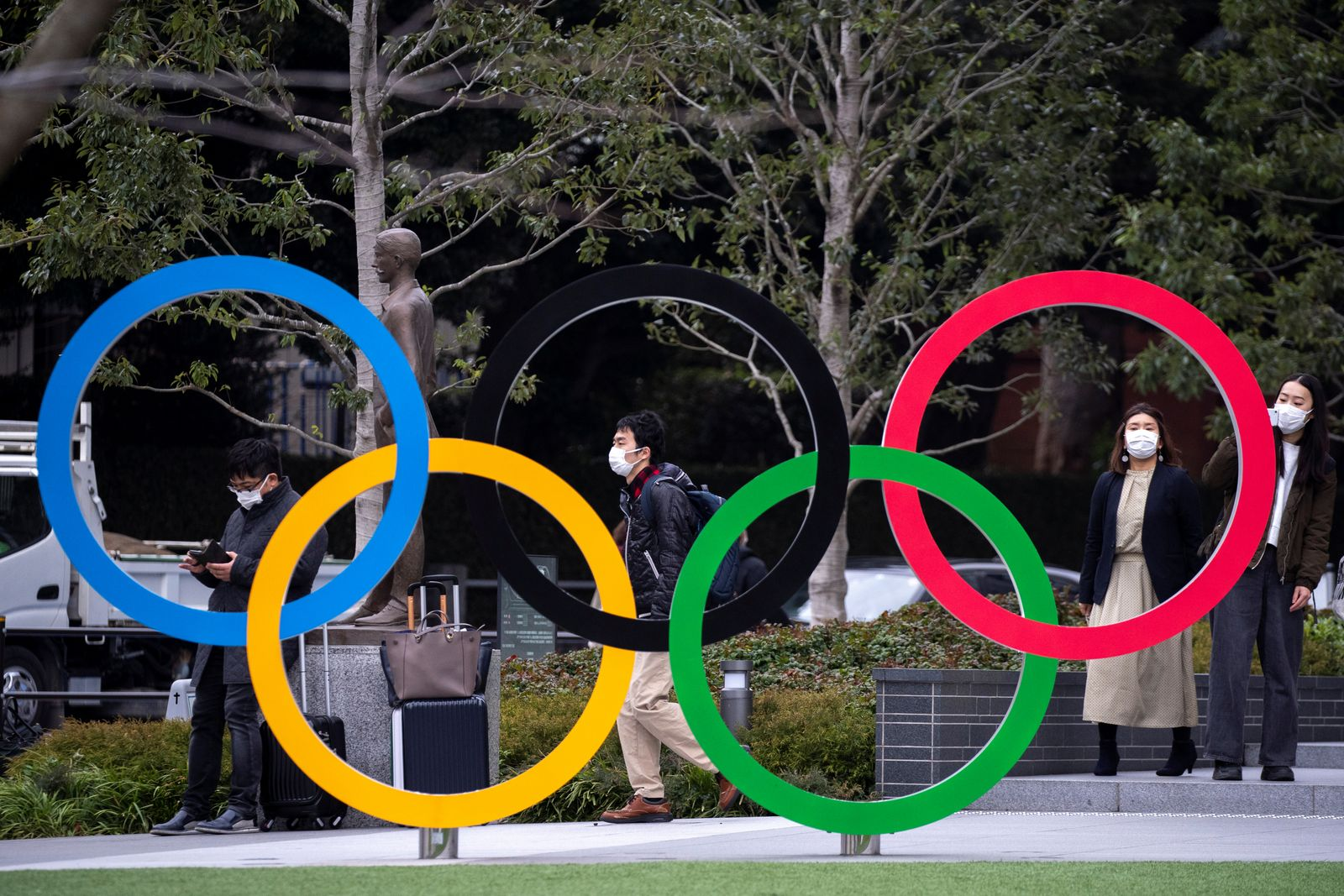 People wearing protective face masks, following an outbreak of the coronavirus, are seen next to the Olympic rings in front of the Japan Olympic Museum in Tokyo