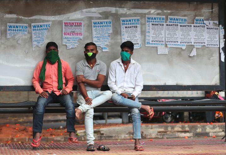 Männer mit Mund-Nasen-Schutz an einer Bushaltestelle in Bengaluru, Indien.