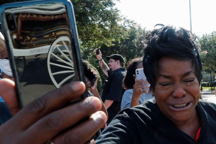 Abschied unter Tränen: Eine Frau fotografiert Floyds Sarg im Leichenwagen
