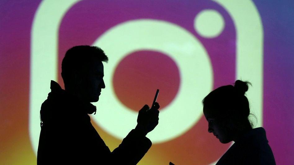 Menschen vor einem Instagram-Logo