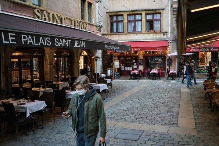 EinMann geht an den leeren Tischen und Stühlen von Restaurants in der französischen Stadt Lyon vorbei