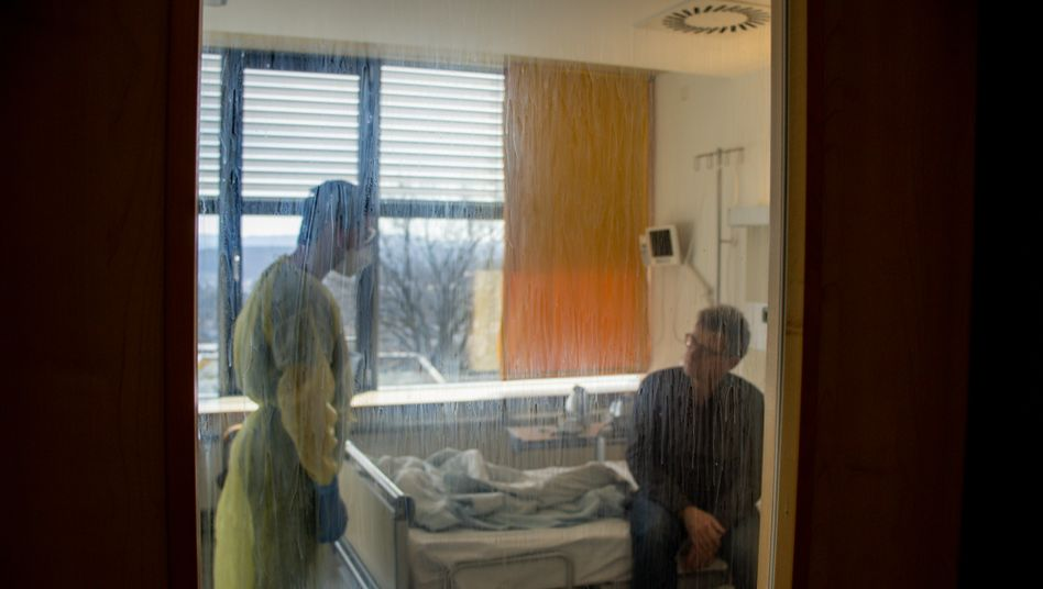 Stefano Fusco, Oberarzt der Isolierstation, im Gespräch mit dem Patienten an der Uniklinik Tübingen, an der Scheibe klebt getrocknetes Desinfektionsmittel