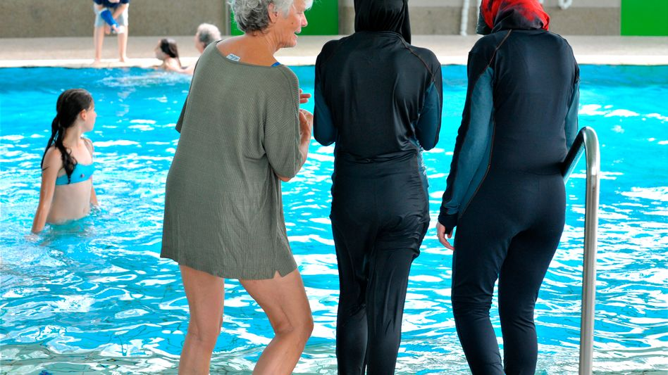 Muslim girls can be seen wearing burqinis at a swimming pool in Freiburg, Germany.