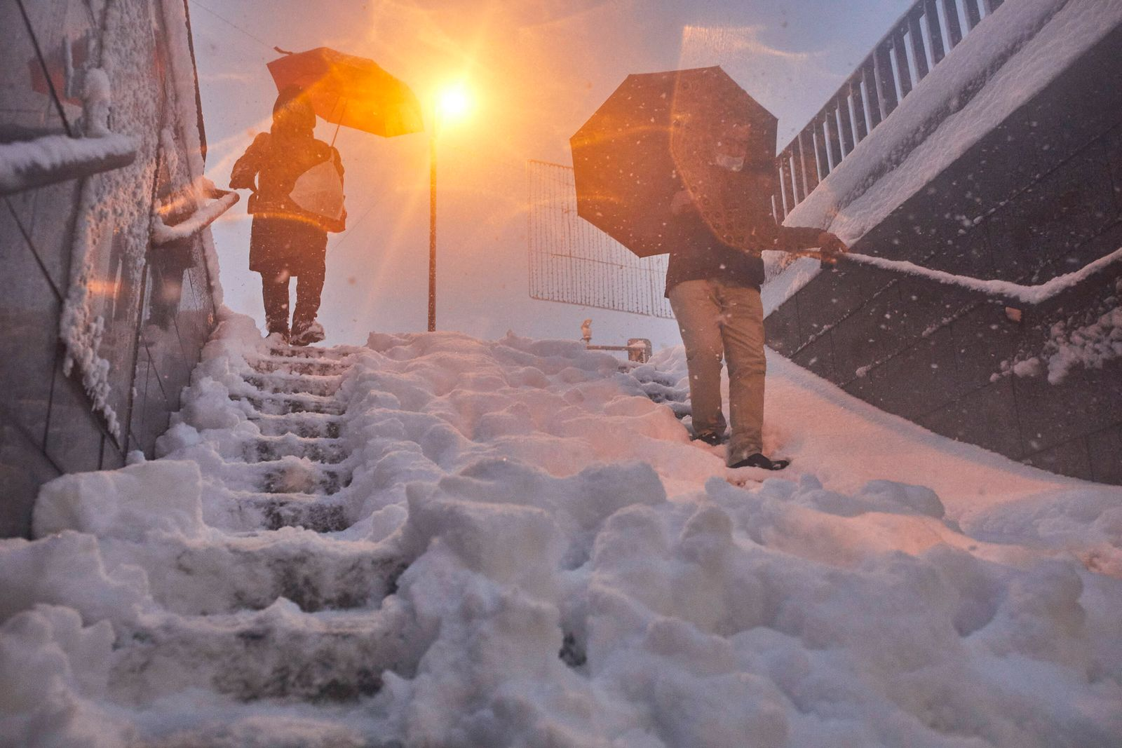 Two people descend a staircase from a snow-covered metro station after passing through the Filomena squall in Madrid (S