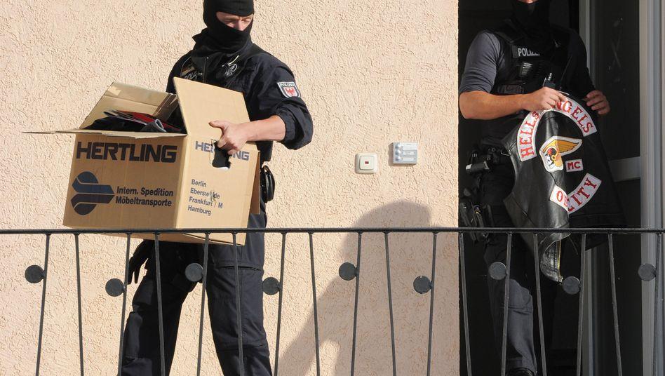 Razzia gegen Rockergruppen: Polizisten tragen in Fürstenwalde beschlagnahmte Gegenstände aus einem Haus