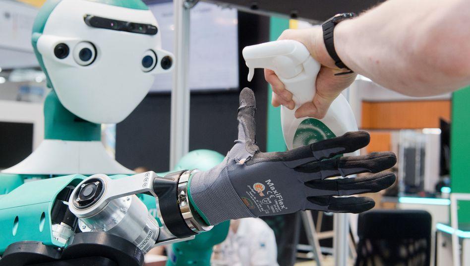 Ein Roboter reicht bei den Aufbauarbeiten für die Messe Cebit ein Putzmittel an (2018)