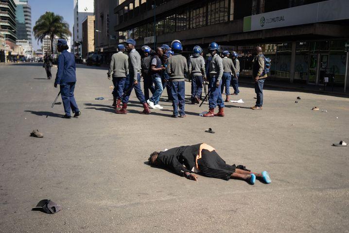 Polizisten in der Innenstadt von Harare am 16. August, davor eine offenbar bewusstlos geschlagene Frau