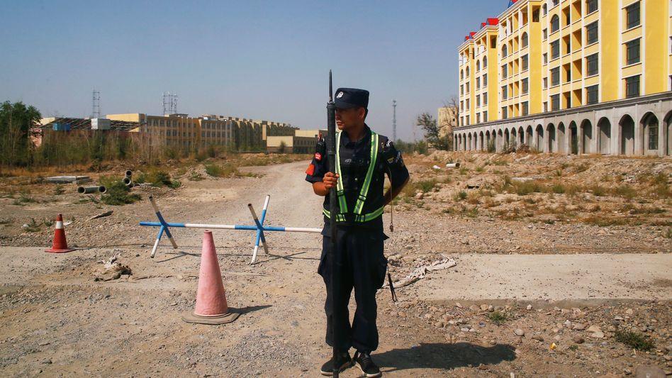 Ein chinesischer Polizist vor einem Umerziehungslager in der autonomen Region Xinjiang (Archivbild)