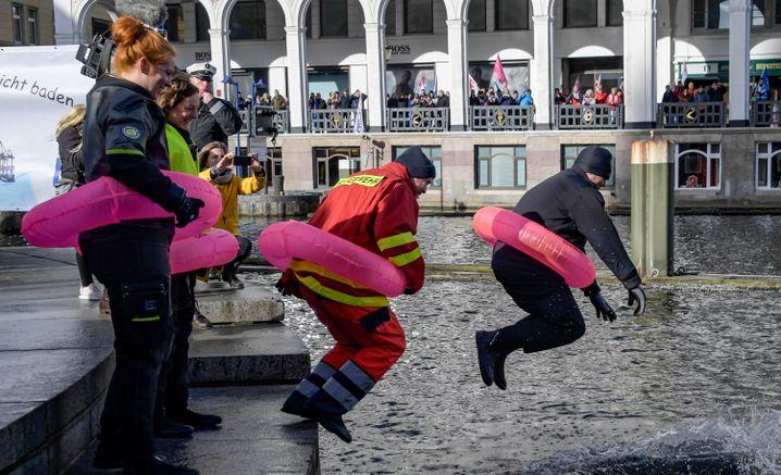 Mitarbeiter im öffentlichen Dienst springen in Hamburg in die Alster.