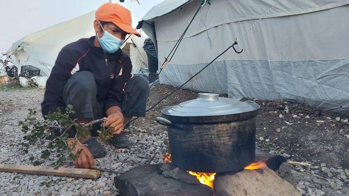 Vater Saeed Qader Musawi kocht heißes Wasser für Tee vor seinem Zelt in Kara Tepe